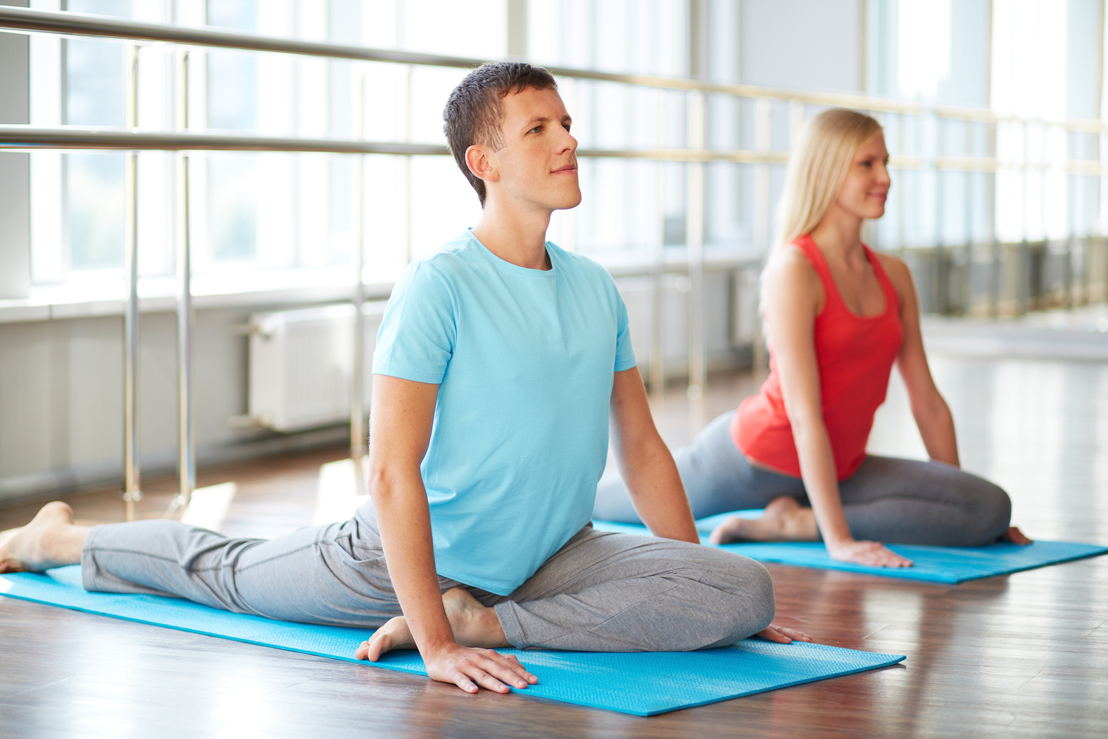 Young man and woman in yoga pose in a Vinayam studio class