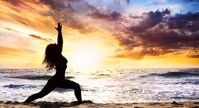Woman doing Sun Salutation yoga pose by ocean with yellow gray clouds across the whole sky
